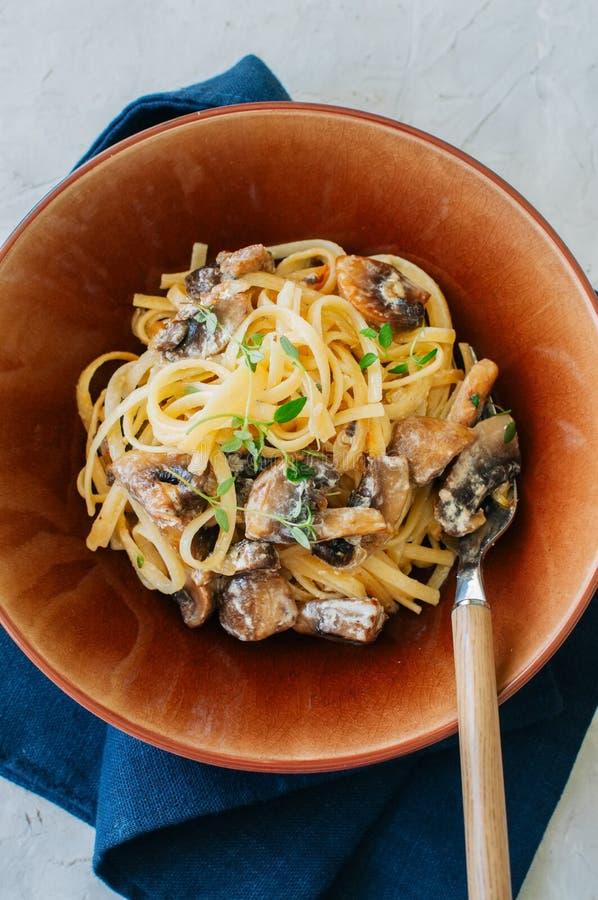 Italienisches Nahrungsmittelkonzept Teigwaren mit Pilzen und sahniger Soße auf w stockfotografie