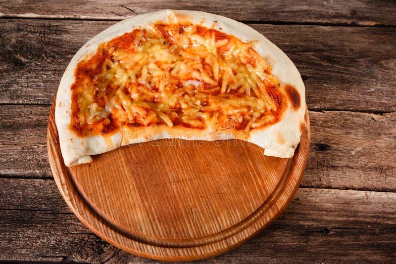Italienisches Pizza calzone gedient auf hölzerner Servierplatte stockbilder