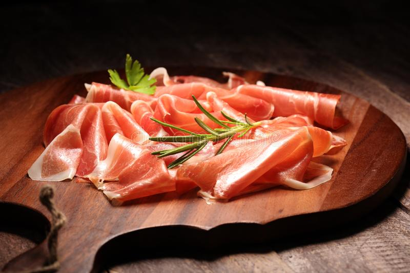 Italienisches Prosciutto crudo oder jamon mit Rosmarin Roher Schinken auf h?lzernem Brett lizenzfreies stockfoto