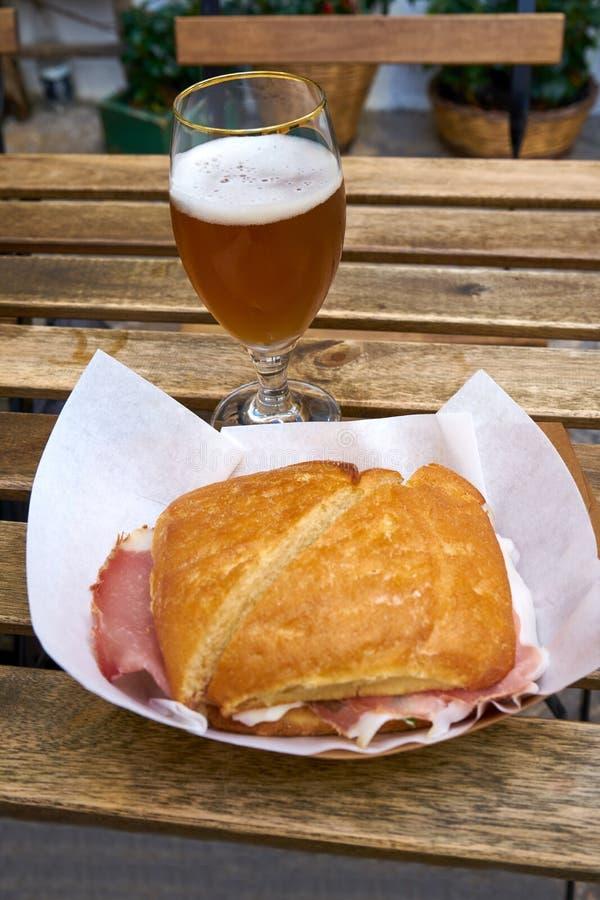 Italienisches Sandwich aus Trockenschinken auf Holztisch mit Bier-Glas stockbilder