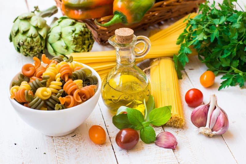 Italienisches Teigwarenspaghettis fusilli, Flasche Olivenöl, Basilikum, Kirschtomaten, Knoblauch, Kräuter und Gemüse, Abendessenb stockfotografie