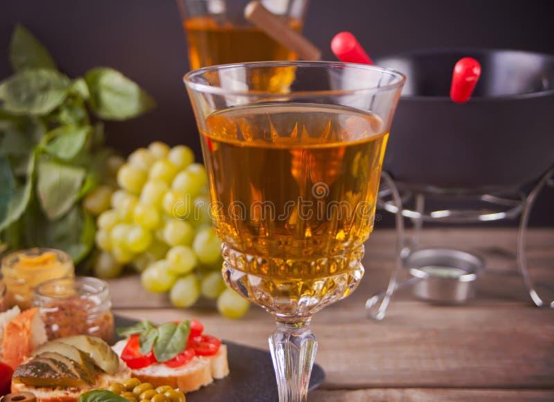 Italiensk bruschetta i sortimentet på plattan, exponeringsglas med vitt vin, druvor, fondue Parti- eller matställebegrepp arkivfoto