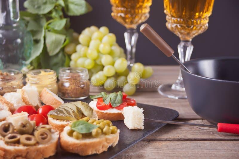 Italiensk bruschetta i sortimentet på plattan, exponeringsglas med vitt vin, druvor, fondue Parti- eller matställebegrepp royaltyfri bild