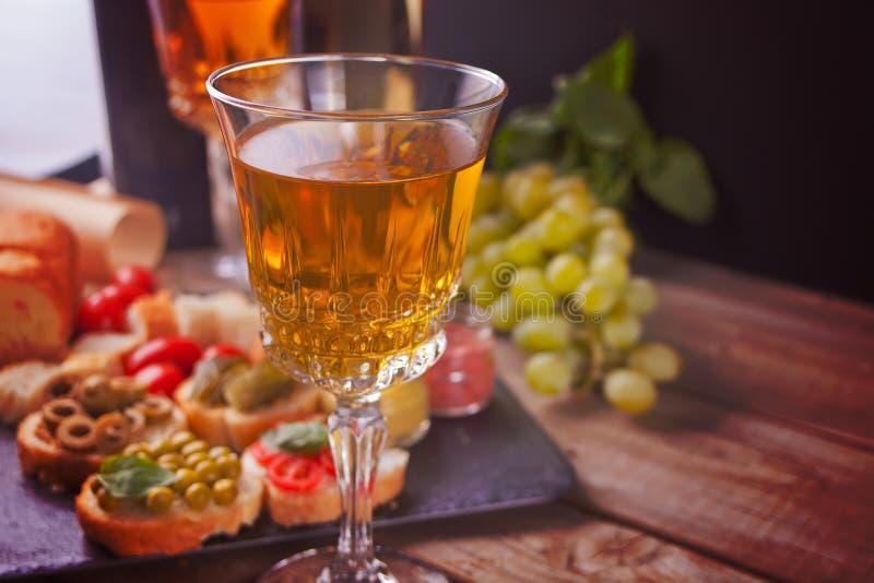 Italiensk bruschetta i sortimentet på plattan, exponeringsglas med vitt vin, druvor Parti- eller matställebegrepp arkivfoto
