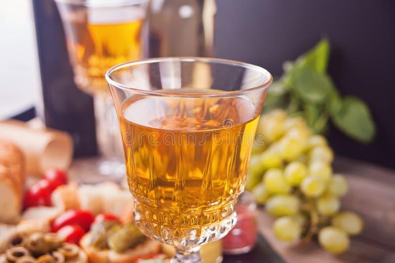 Italiensk bruschetta i sortimentet på plattan, exponeringsglas med vitt vin, druvor Parti- eller matställebegrepp fotografering för bildbyråer