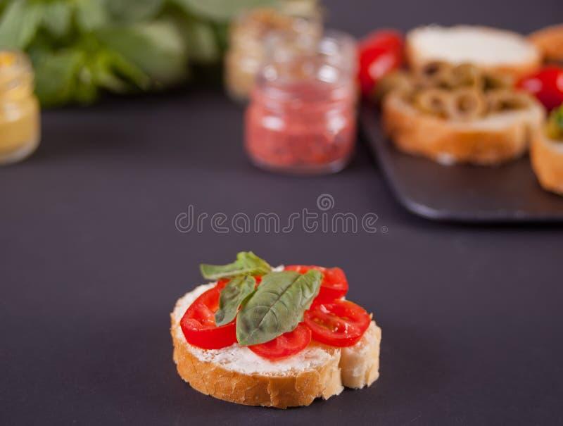 Italiensk bruschetta med gräddost, tomatkörsbär och bazil och bruschetta i sortiment på plattan med uppsättningen med den lilla f royaltyfria bilder