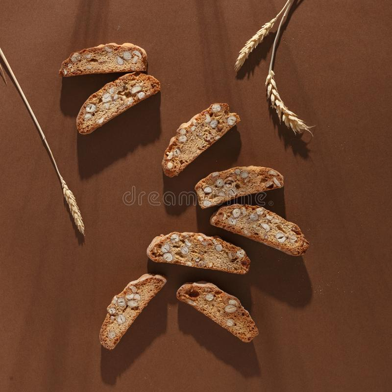 Italiensk cantuccinikaka med mandelfyllning och vete på brun bakgrund Top beskådar royaltyfri foto