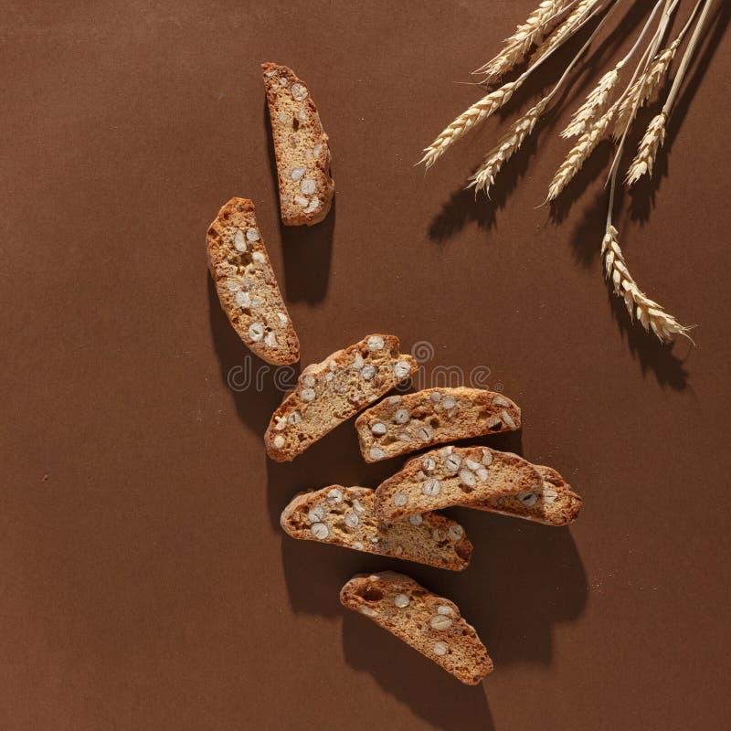 Italiensk cantuccinikaka med mandelfyllning och vete p? brun bakgrund Top besk?dar royaltyfri foto