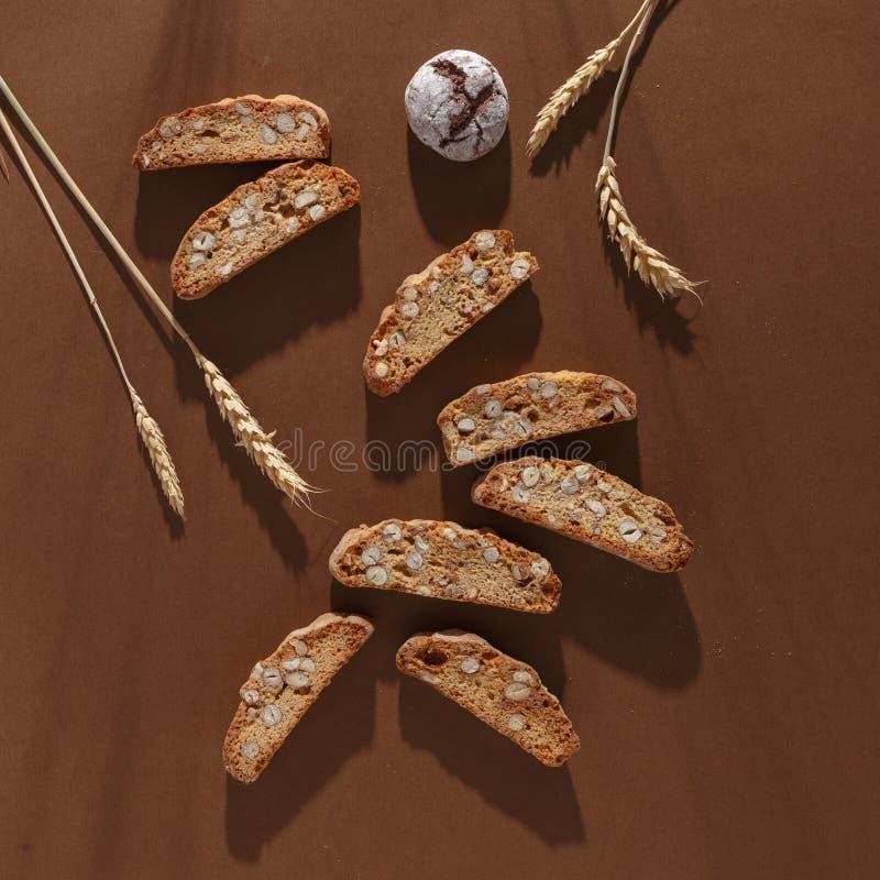 Italiensk cantuccinikaka med mandelfyllning och vete p? brun bakgrund Top besk?dar arkivfoton