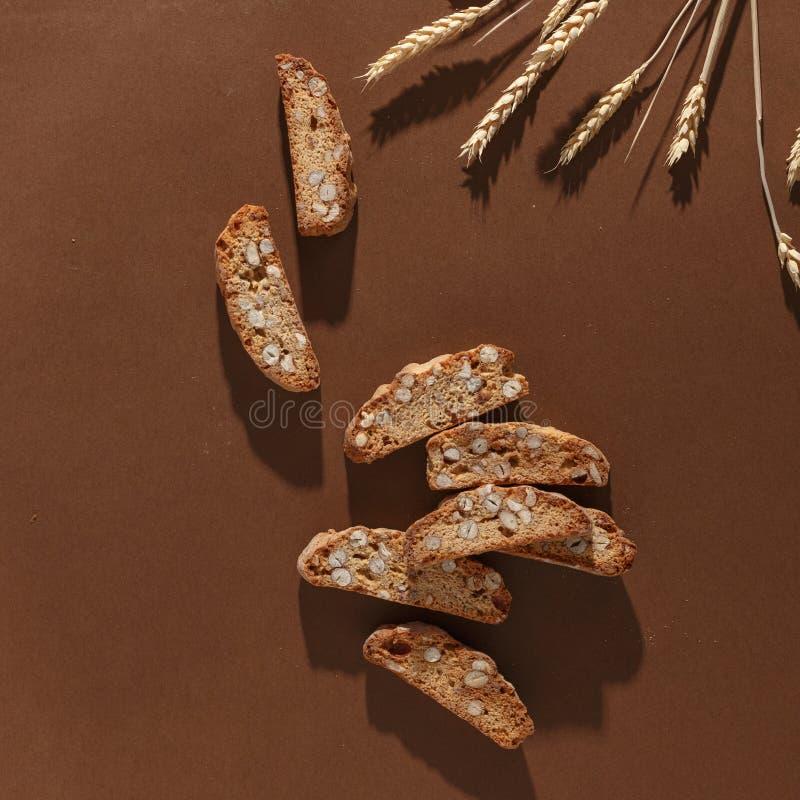 Italiensk cantuccinikaka med mandelfyllning och vete p? brun bakgrund Top besk?dar arkivbild