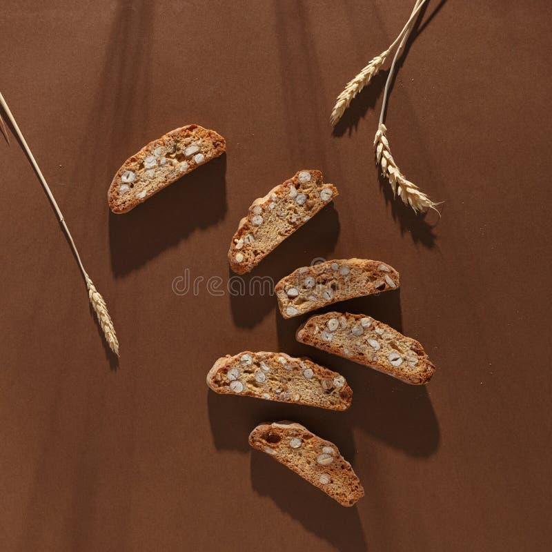 Italiensk cantuccinikaka med mandelfyllning och vete p? brun bakgrund Top besk?dar royaltyfria bilder