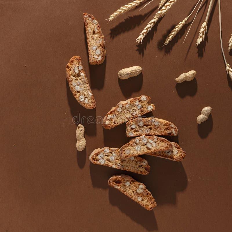 Italiensk cantuccinikaka med mandelfyllning, vete och muttrar p? brun bakgrund Top besk?dar royaltyfria foton