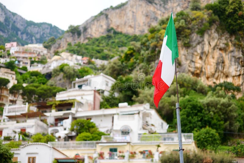 Italiensk flagga över härlig stad av Positano på den berömda Amalfi kusten royaltyfri bild