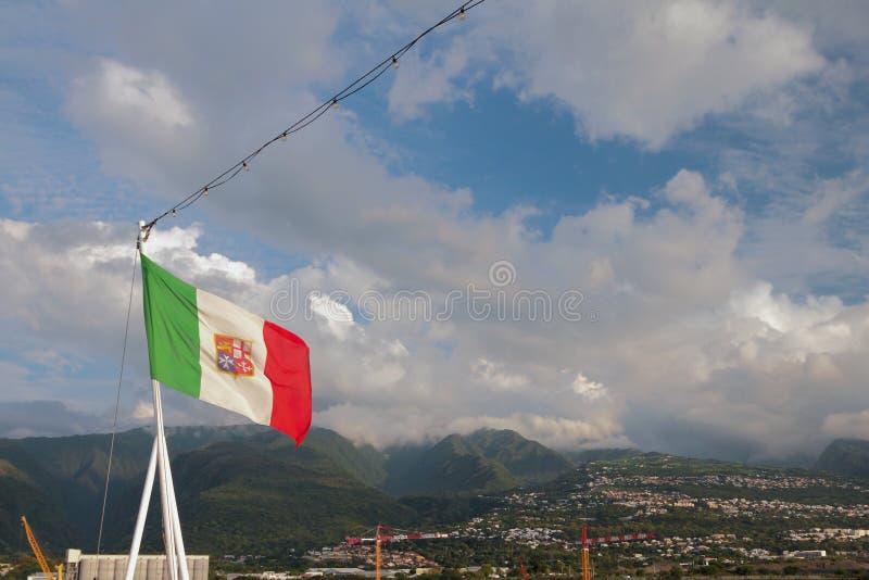 Italiensk flagga med maltesisk symbolics mot bakgrund av bergig terräng Boeuf-mort möte royaltyfria bilder