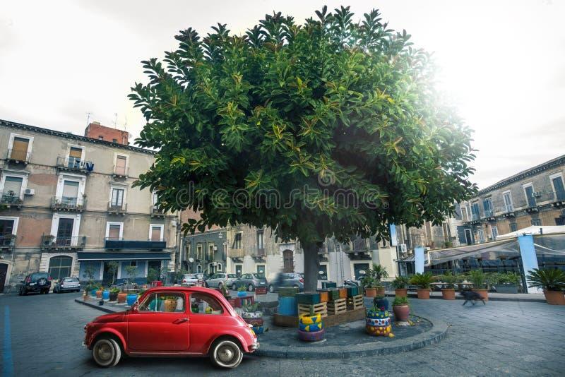Italiensk gammal röd bil som parkeras nära ett träd i en fyrkant i staden av Catania i Italien fotografering för bildbyråer
