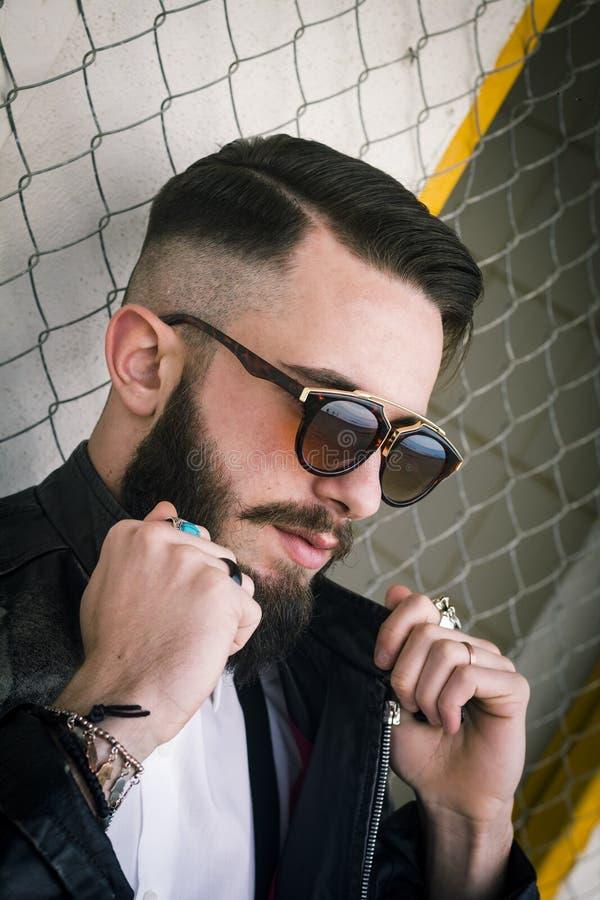 Italiensk grabb med exponeringsglas och långt skägg - stilig pojke med solglasögon royaltyfri foto