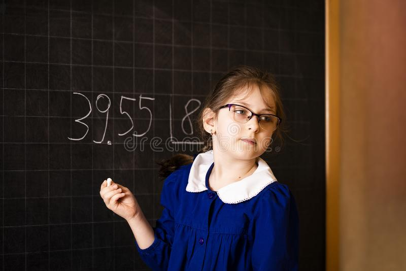Italiensk grundskolaflicka som f?rs?ker att l?sa exempel f?r en matematik som g?r en l?ng uppdelning p? svart tavla royaltyfria bilder
