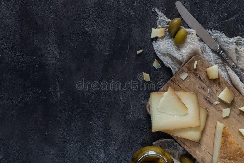 Italiensk hårdostpecorinotoscano som skivas och huggas av på träbräde med kniven och gröna oliv, kopieringsutrymme royaltyfri foto
