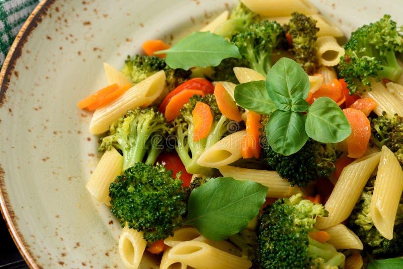 Italiensk husmanskost Grönsakpasta med broccoli, körsbärsröd toma arkivfoto
