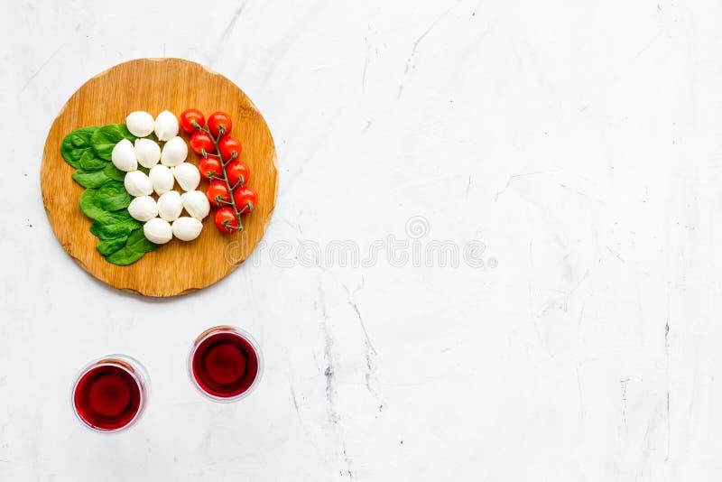 Italiensk kokkonst, matbegrepp Italiensk flagga som göras av mozzarellaen, tomater, basilika på träskärbräda nära exponeringsglas fotografering för bildbyråer