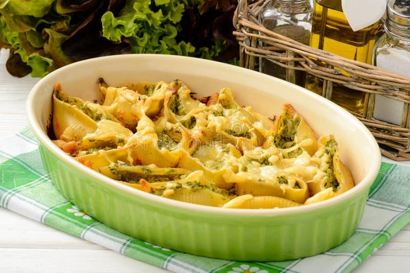 Italiensk kokkonst - pasta beskjuter välfyllt med spenat, ricotta och bakat med tomater fotografering för bildbyråer