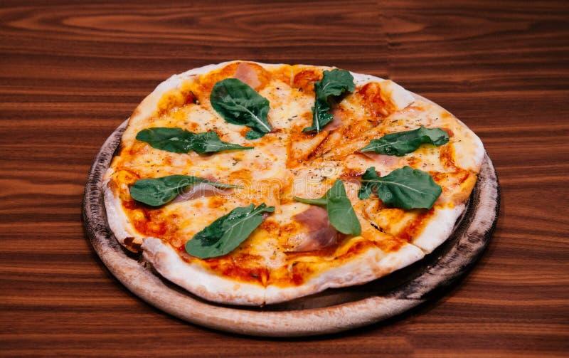 Italiensk margheritapizza med basilika för parma skinka på den wood tabellen royaltyfria foton