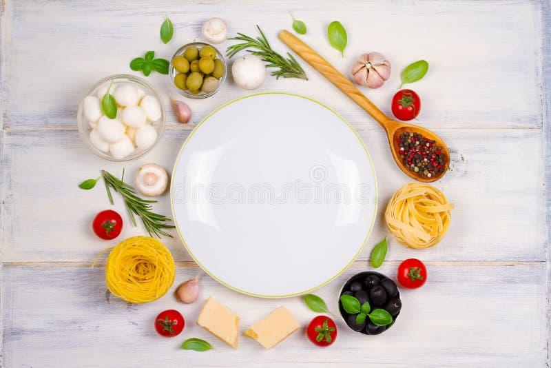 Italiensk mat eller ingredienser med nya grönsaker, pasta, ostmozzarellaen och parmesan, kryddor arkivbilder