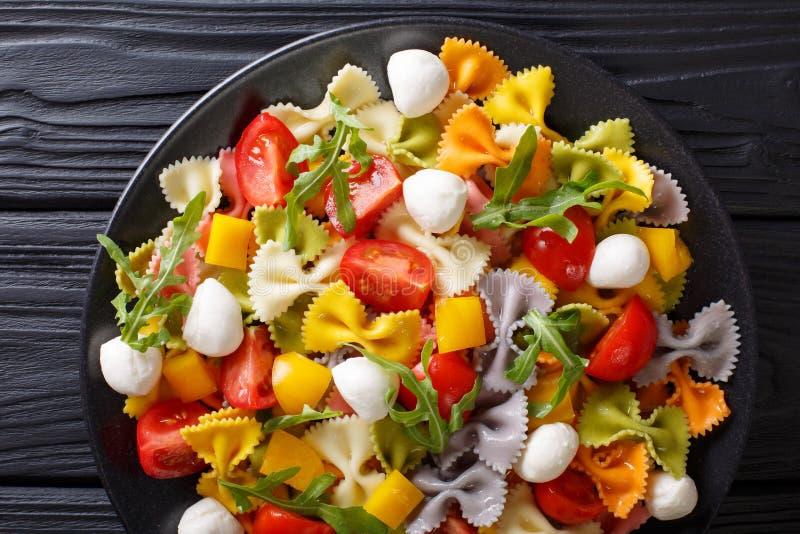 Italiensk mat: farfallepasta med grönsaker och mozzarellaclos royaltyfri bild