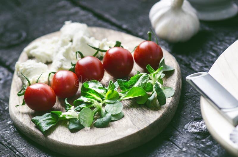 Italiensk mat, kokkonst Margherita pizza på en svart, trätabellen med igredients gillar tomater, sallad, ost, mozzarellaen, basil royaltyfria bilder