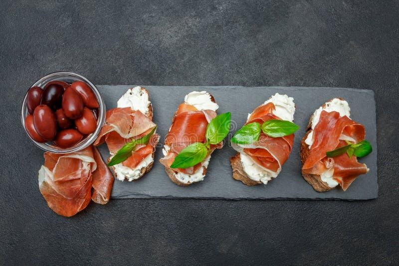 Italiensk mat med oliv och prosciuttobruschettas på stenen stiger ombord arkivfoton