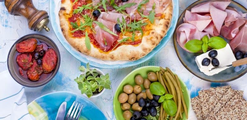 Italiensk mat på tabellen, pizza och antipastoen Härlig portion för en familjmatställe Oliv och basilika Ost och skinka royaltyfri bild