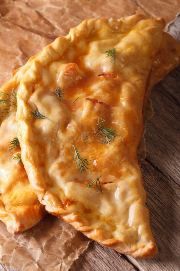 Italiensk mat: pizzacalzonenärbild på tabellen Lodlinjeöverkant royaltyfri fotografi