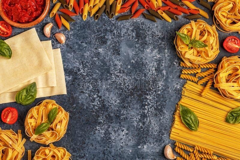 Italiensk matbakgrund med pasta, kryddor och grönsaker arkivfoton