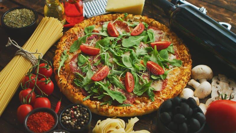 Italiensk matbakgrund med pizza, rå pasta och grönsaker på trätabellen royaltyfri bild