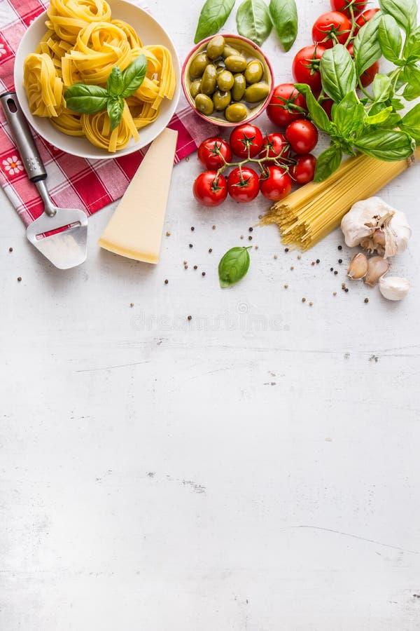 Italiensk matkokkonst och ingredienser på vitbetongtabellen Ost för parmesan för tomater för olivolja för spagettitagliatelleoliv fotografering för bildbyråer
