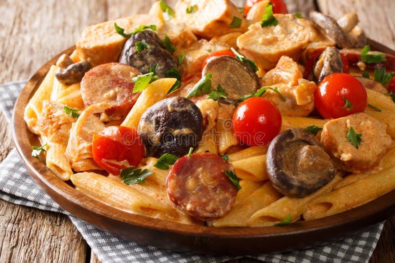 Italiensk matpennepasta med höna, lösa champinjoner, rökt korv med krämig närbild för ostsås på en platta på tabellen arkivfoton