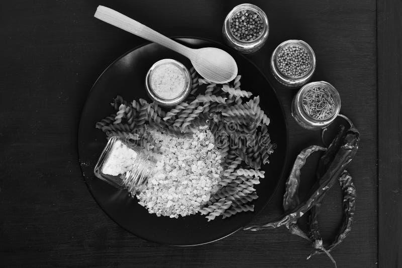 Italiensk maträtt som förläggas på den mörka trätabellen Krus av kryddor royaltyfri fotografi