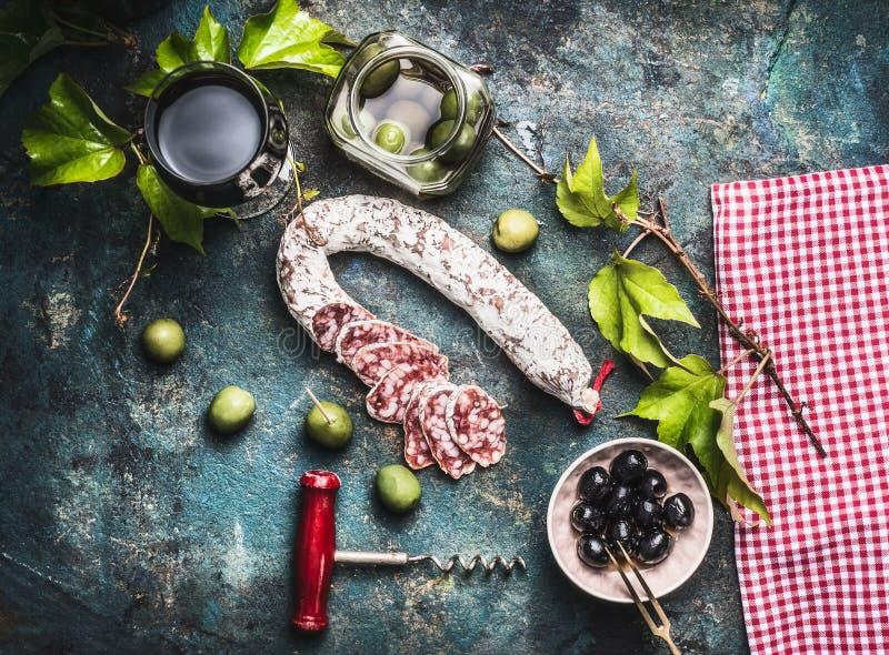 Italiensk matstilleben med exponeringsglas av rött vin, oliv och korven på lantlig bakgrund royaltyfria bilder