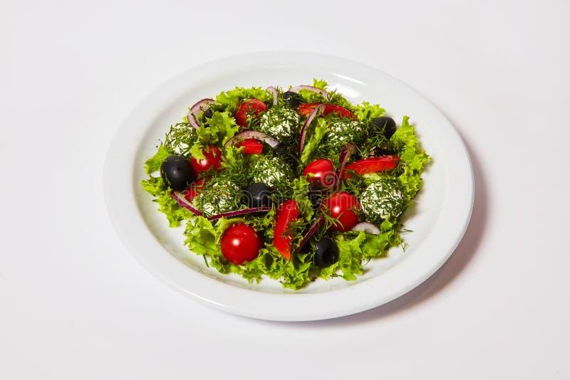 Italiensk ost klumpa ihop sig sallad med tomater och nya grönsaker på plattan royaltyfri foto