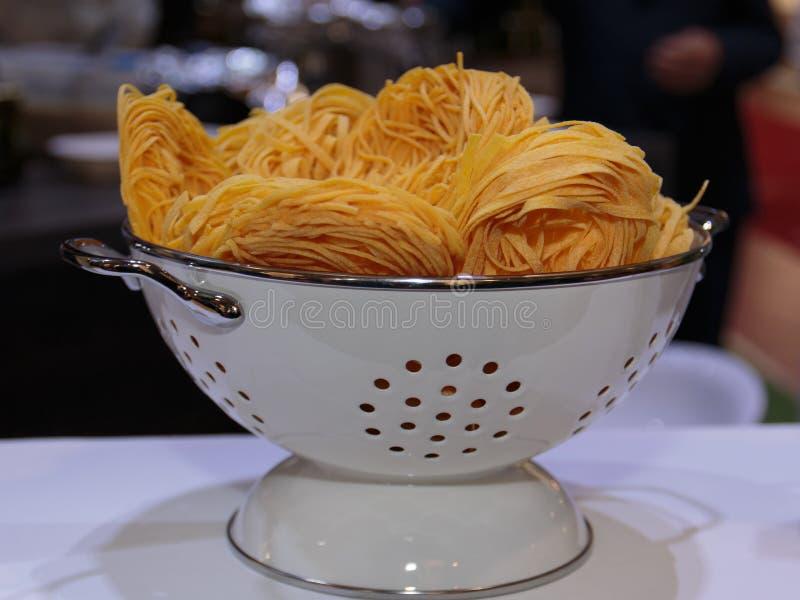 Italiensk pasta för okokt tagliatelle inom den vita durkslaget arkivbilder