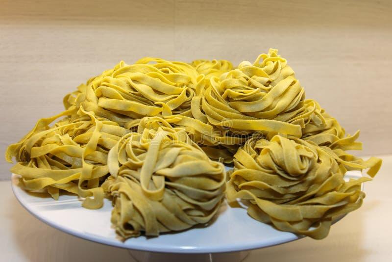 Italiensk pasta för okokt tagliatelle som visas på den vita maträtten royaltyfria foton