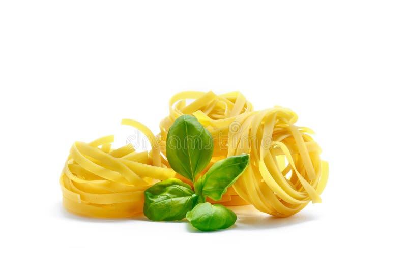 Italiensk pasta för tagliatelle med basilika som isoleras på vit bakgrund royaltyfri foto