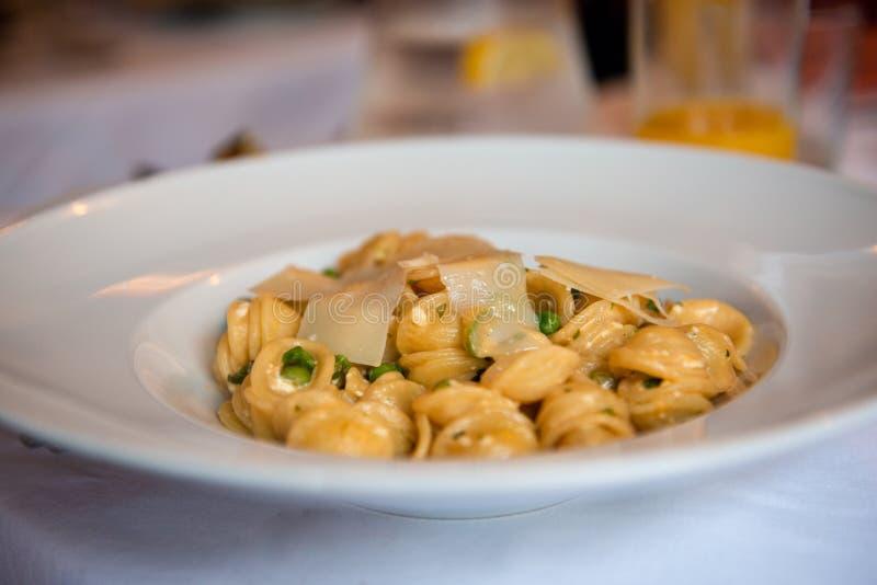 Italiensk pasta med ärtor och parmesan arkivbilder