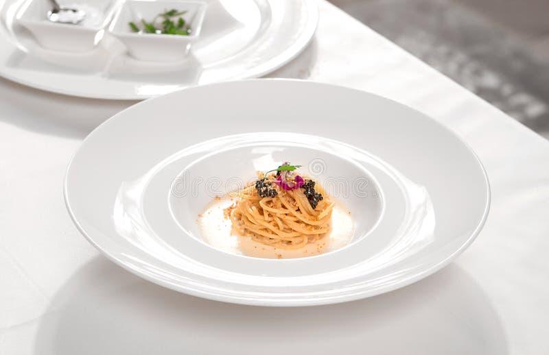 Italiensk pasta med den svarta kaviaren och kräm arkivbilder