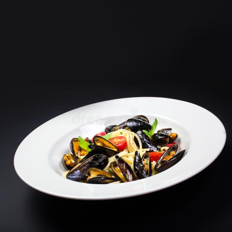 Italiensk pasta med musslamarinara, körsbärsröda tomater och örter f royaltyfri bild