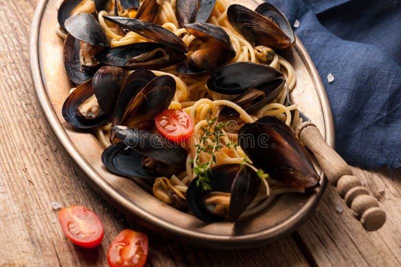 Italiensk pasta med musslor i svarta skal och att klippa tomater i guld- platta för metall arkivfoto