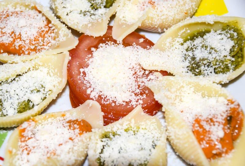 Italiensk pasta med pestotomaten och parmesan på en platta fotografering för bildbyråer