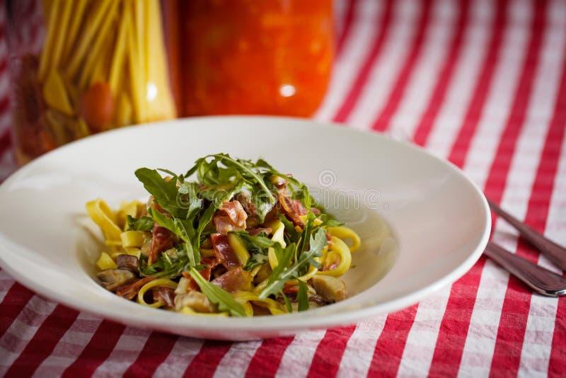 Italiensk pasta med raketsallad och skinka på tabellen royaltyfria bilder
