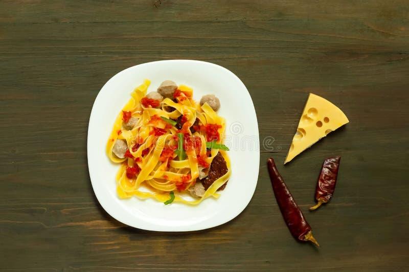 Italiensk pasta med tomatsås och köttbullar i en vit platta på en träbakgrund Begrepp av populär amerikansk spagetti arkivbild
