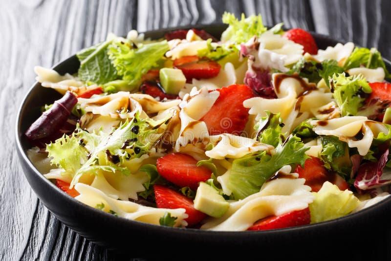 Italiensk pastafarfalle med avokadot, jordgubbar, grönsallat och balsamic såsnärbild på en platta horisontal royaltyfria bilder